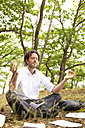 Germany, businessman in forest surrounded by papers practising yoga - MFRF000251