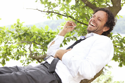 Germany, relaxed businessman lying in tree smoking a joint - MFRF000262