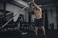 Physical athlete exercising with barbell - MADF000445