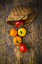 Wickerbasket and different tomatoes on wood - LVF003717