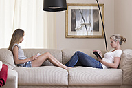 Mother and daughter sitting with digital tablet and book on the couch - SGF001794
