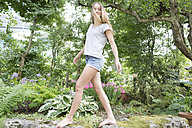 Blond teenage girl balancing on wall in a garden - SGF001792