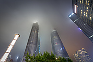 China, Shanghai, Jin Mao Building, World Financial Center and Shanghai Tower sticking in low clouds at night - NKF000326