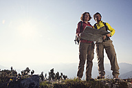 Austria, Tyrol, couple standing with map at Unterberghorn - RBF002978