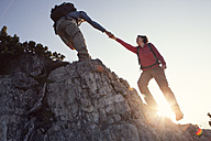 Austria, Tyrol, Unterberghorn, man helping woman on hiking trip - RBF002930