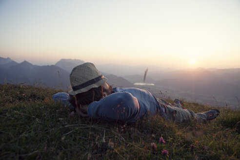 Austria, Tyrol, Unterberghorn, man relaxing on alpine meadow at sunset - RBF002947