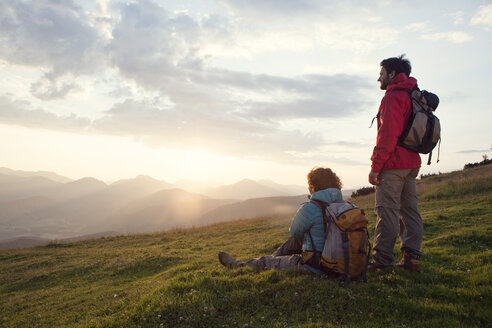 Austria, Tyrol, Unterberghorn, two hikers resting in alpine landscape at sunrise - RBF002967