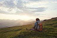 Austria, Tyrol, Unterberghorn, hiker resting in alpine landscape at sunrise - RBF002968