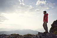 Austria, Tyrol, Unterberghorn, hiker standing in alpine landscape looking at view - RBF002973