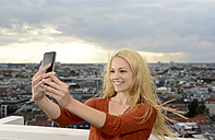Germany, Berlin, young woman taking a selfie with her smartphone - BFRF001401