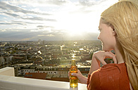 Germany, Berlin, young woman with beverage looking at view - BFRF001404