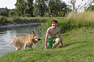 Smiling teenage boy and a Golden Retriever after bathing - LBF001147