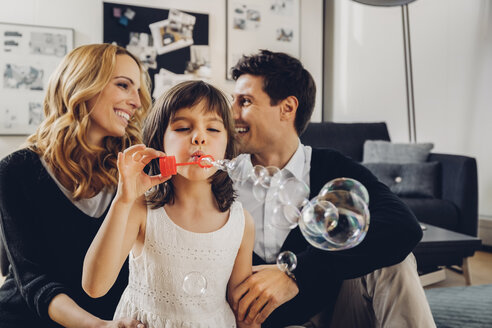 Happy family at home with girl blowing soap bubbles - CHAF000983