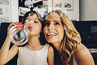 Happy mother with daughter at home blowing soap bubbles - CHAF000986