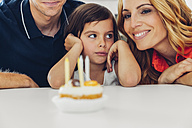 Family with daughter celebrating birthday with candles on cake - CHAF000989