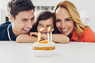 Family with daughter celebrating birthday with candles on cake - CHAF000992