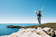 Bolivia, La Paz Department, Happy woman with raised arms on top of Isla del sol on Lake Titicaca - GEMF000294