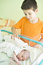 Boy watching his newborn sister in a hospital - DEGF000475