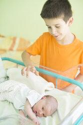 Boy watching his newborn sister in a hospital - DEGF000475