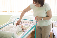 Senior woman watching her newborn granddaughter in a hospital - DEGF000476