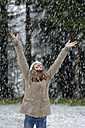 Girl enjoying snow fall, beginning of winter - LBF001143