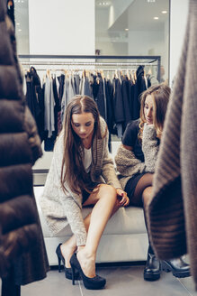 Two young women shopping for shoes in a boutique - CHAF001335
