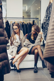 Two young women shopping for shoes in a boutique - CHAF001336