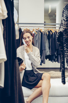 Smiling young woman on cell phone in a boutique - CHAF001339