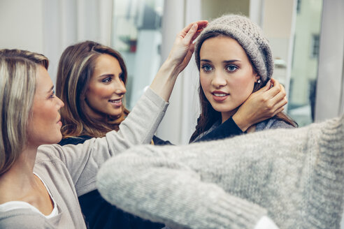 Young woman putting on woolly hat in a boutique assisted by two women - CHAF001346
