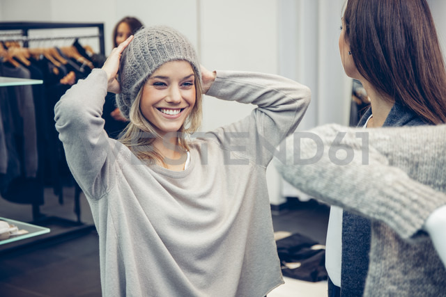 Happy oung woman putting on woolly hat in a boutique - CHAF001348