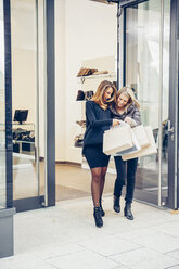 Two happy young women with shopping bags leaving a boutique - CHAF001352