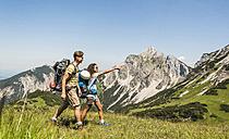Austria, Tyrol, Tannheimer Tal, young couple hiking on alpine meadow - UUF005049
