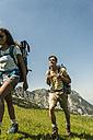 Austria, Tyrol, Tannheimer Tal, young couple hiking on alpine meadow - UUF005055
