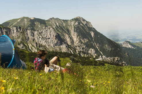 Austria, Tyrol, Tannheimer Tal, young couple resting next to tent on alpine meadow - UUF005062
