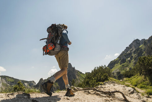 Austria, Tyrol, Tannheimer Tal, young man hiking on mountain trail - UUF005067