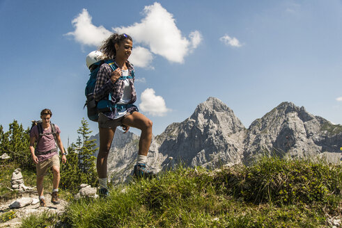 Austria, Tyrol, Tannheimer Tal, young couple hiking on mountain trail - UUF005072