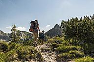 Austria, Tyrol, Tannheimer Tal, young couple hiking on mountain trail - UUF005074