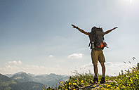 Austria, Tyrol, Tannheimer Tal, young man standing on mountain trail with arms outstretched - UUF005082