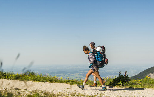 Austria, Tyrol, Tannheimer Tal, young couple hiking on mountain trail - UUF005085