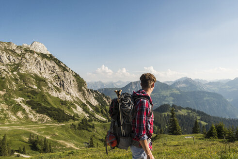 Austria, Tyrol, Tannheimer Tal, young man hiking on alpine meadow - UUF005088