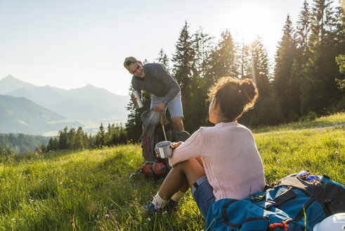 Austria, Tyrol, Tannheimer Tal, young couple resting on alpine meadow - UUF005118