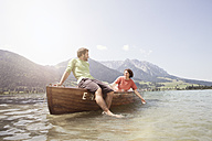 Austria, Tyrol, couple relaxing on a boat on Walchsee - RBF002987