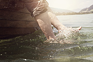 Austria, Tyrol, woman's feet splashing in water of Walchsee - RBF002984