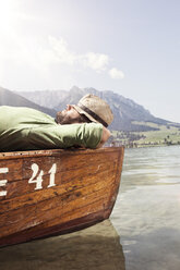 Austria, Tyrol, man relaxing on a boat on Walchsee - RBF002986