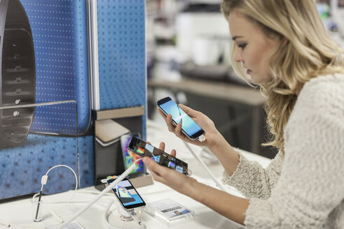 Young woman comparing two smartphones in a shop - ZEF007349