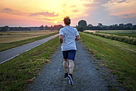 Rear view of man jogging at sunset - PUF000390
