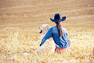 Back view of young woman and Golden Retriever sitting on a stubble field - MAEF010825