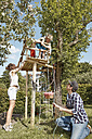 Family playing at tree house in garden - RHF000988