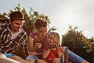 Happy family relaxing in garden - RHF001035