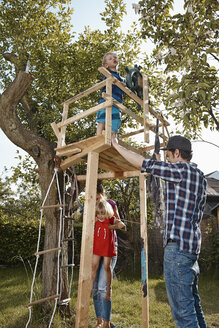 Family playing in garden at tree house - RHF001015